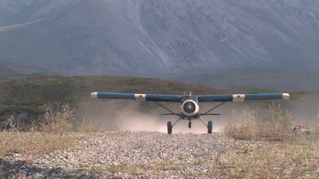 a blue and white single-propeller airplane with the a mountain base in the background. - arctic national wildlife refuge stock videos & royalty-free footage