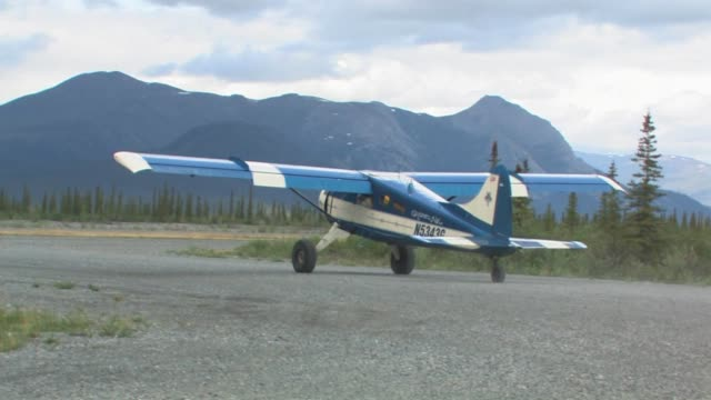 a blue and white single-propeller airplane with the brooks range in the background. - arctic national wildlife refuge stock videos & royalty-free footage