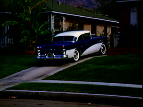 Blue and white twotone Buick Century twodoor hardtop with whitewall tires driving along quaint suburban neighborhood street passing by manicured...