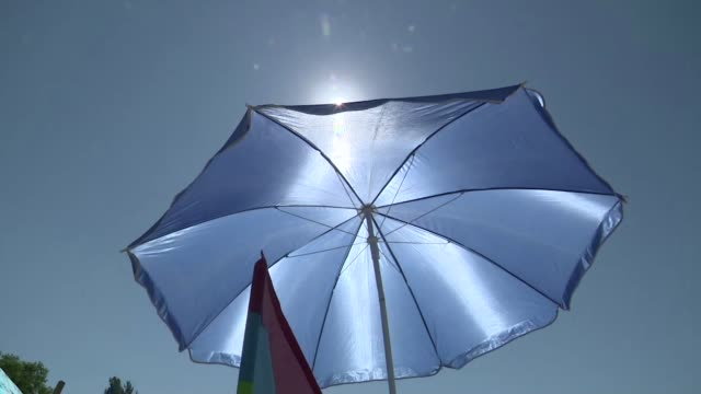 blue beach umbrella - sonnenschirm stock-videos und b-roll-filmmaterial