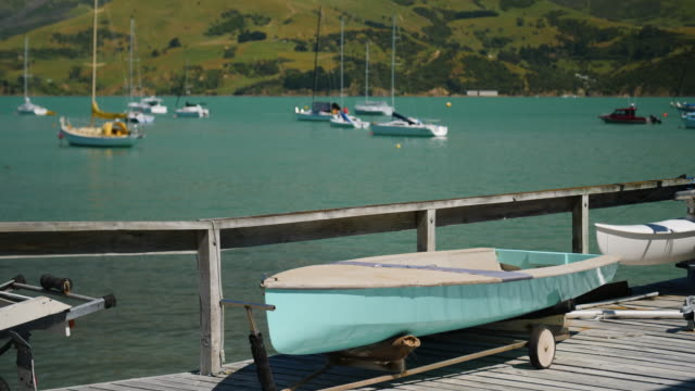 a blue boat sits on a wooden jetty in a sunny harbour - akaroa stock videos & royalty-free footage