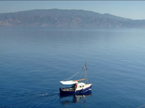 vídeos de stock e filmes b-roll de blue bottomed boat sails along dead calm sea - embarcação comercial