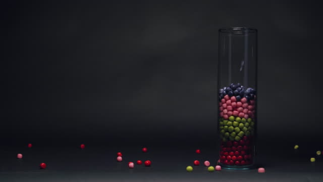 blue candy falling down on top of pink and red and green candy in glass vase in slow motion with copy space on a black chalkboard texture background - blackboard stock videos & royalty-free footage