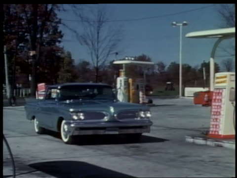 1962 pan blue car pulls into gas station + stops at gas pumps - filling station attendant stock videos & royalty-free footage