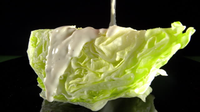 cu blue cheese salad dressing poured over iceberg lettuce wedge and bacon bits sprinkled on top  - salad dressing stock videos & royalty-free footage