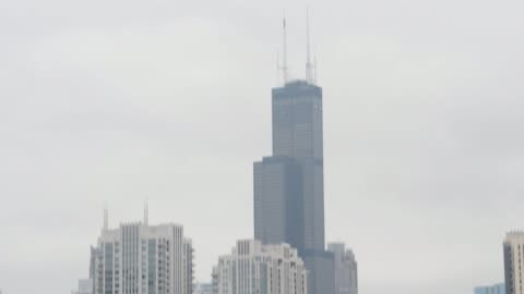 blue chicago tribune delivery vans sit parked in a lot outside the printing facility in chicago, illinois, shots pan down from the willis tower to a... - torre del tribune video stock e b–roll