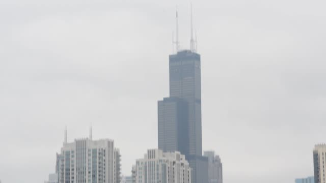 blue chicago tribune delivery vans sit parked in a lot outside the printing facility in chicago illinois shots pan down from the willis tower to a... - tribune tower stock-videos und b-roll-filmmaterial