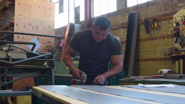 Blue collar cutting metal in factory