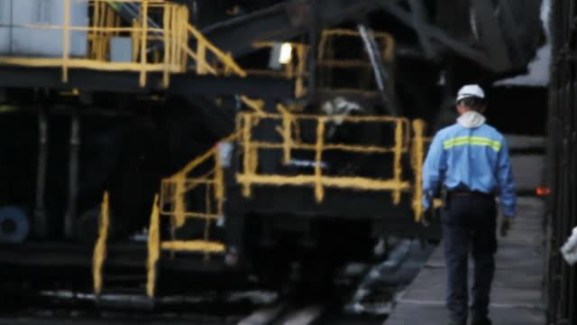 Blue collar industrial worker walking through intense heat away from camera