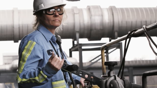 Blue collar woman industrial worker operating equipment