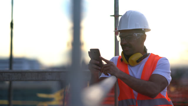 Blue collar worker at a construction site taking a break leaning on a scaffold while chatting on his smartphone smiling
