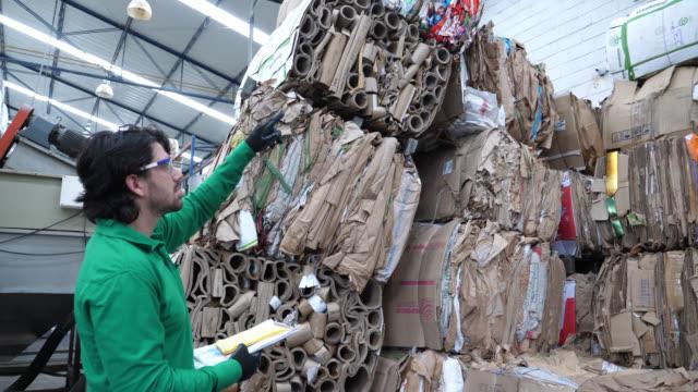 Blauwe kraag werknemer in een recycling fabriek tellen de stack van kartonnen materiaal en schrijven it down op een Klembord