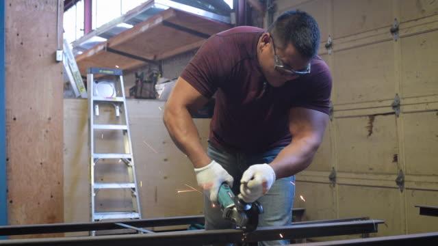 Blue collar worker cutting metal