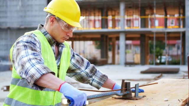vidéos et rushes de ouvrier sur le chantier de construction, des bandes d'armature - ingénierie