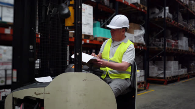 blue collar worker on forklift preparing a shipment order looking at clipboard - world trade organisation stock videos & royalty-free footage