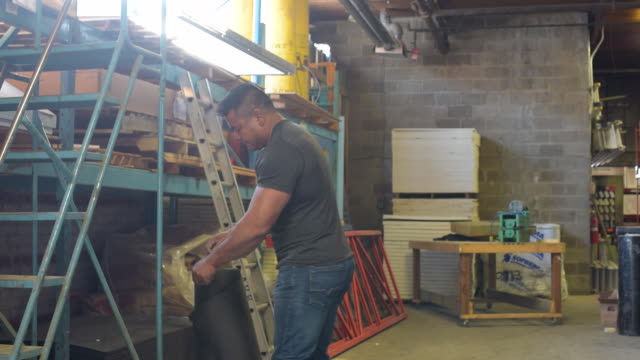 vidéos et rushes de blue collar worker picking up roll of tar paper in warehouse - tôle