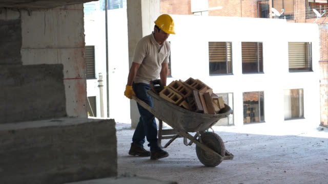 blue collar worker pushing a wheelbarrow full of bricks at a housing project on construction - wheelbarrow stock videos and b-roll footage