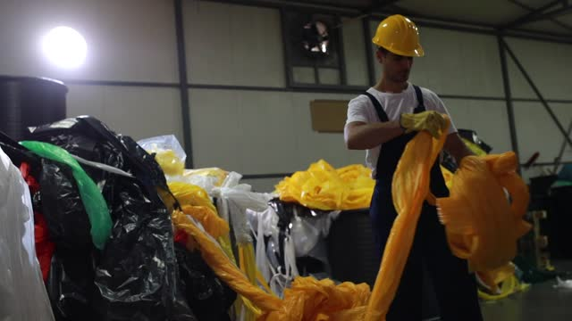 リサイクルプロセスのためにプラスチック廃棄物を分離するブルーカラー労働者 - ゴミ袋点の映像素材/bロール