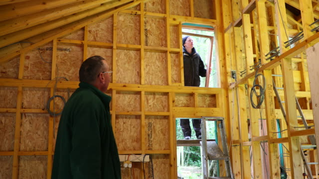 blue collar workers fitting a window - treehouse stock videos & royalty-free footage