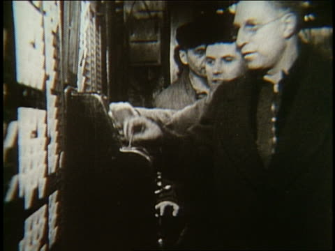 b/w blue collar workers punching time clock - arbeiter stock-videos und b-roll-filmmaterial