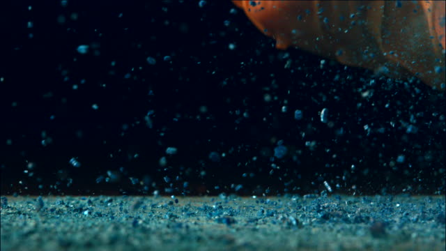 A blue colored rust powder falling and scattering