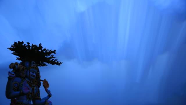vidéos et rushes de a blue colored shiva statue under clouds, india - statue