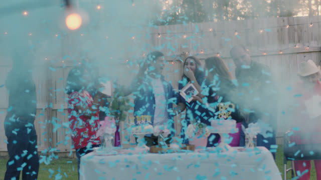 slo mo. blue confetti bomb reveals it's a boy during gender reveal party - party social event stock videos & royalty-free footage