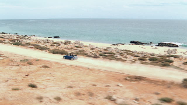 a blue convertible drives on a coastal highway in mexico. - blue convertible stock videos & royalty-free footage