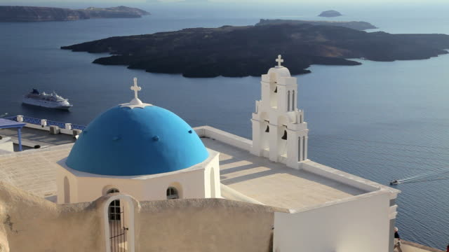 blue dome of the local church and the white washed houses of thira at overlooking the aegean sea on the island of santorini, greece, europe - 白しっくい塗点の映像素材/bロール