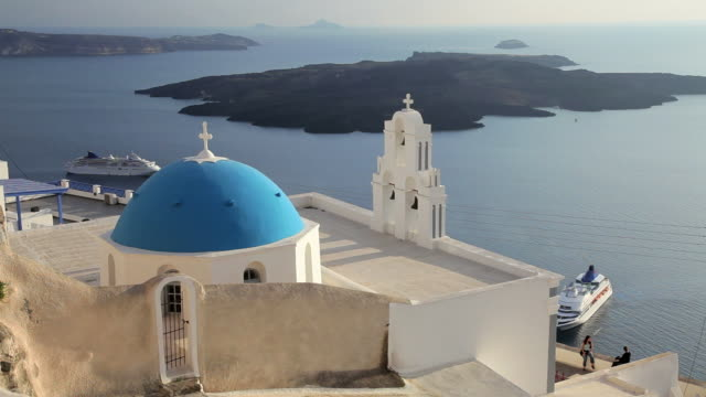 stockvideo's en b-roll-footage met blue dome of the local church and the white washed houses of thira at overlooking the aegean sea on the island of santorini, greece, europe - oia santorini
