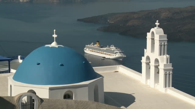 ws blue dome of whitewashed church with cruise ship in background / firostefani, santorini, greece - 白しっくい塗点の映像素材/bロール