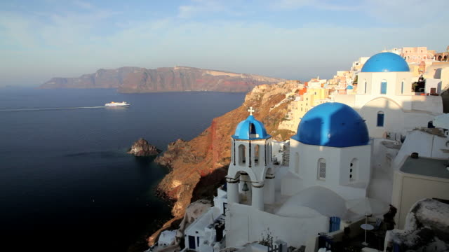 vídeos de stock, filmes e b-roll de blue domed white washed churches of oia overlooking the aegean sea and ferry on the island of santorini, greece, europe - oia santorini