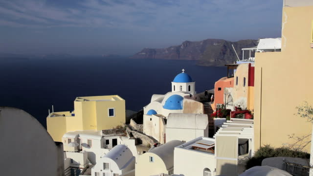 blue domed white washed churches of oia overlooking the aegean sea and ferry on the island of santorini, greece, europe - 白しっくい塗点の映像素材/bロール