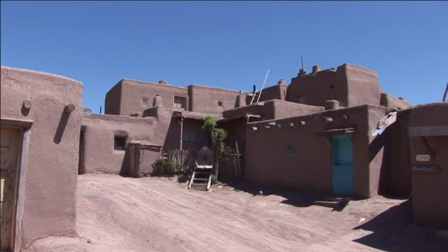 a blue door stands out against a brown adobe building in taos pueblo. - adobe bildbanksvideor och videomaterial från bakom kulisserna