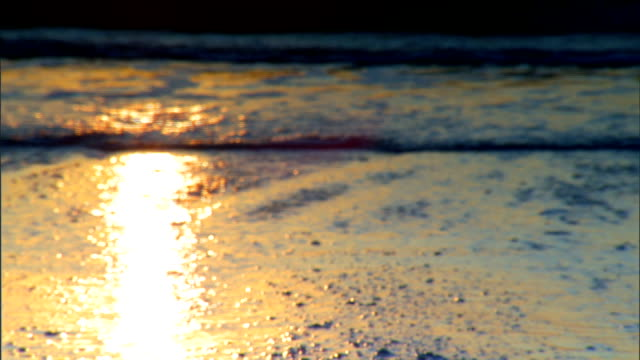 SOFT Slightly orange sunlight reflection on receeding water on beach IN FOCUS Small waves rolling in incoming tide water roll higher covering sand St...