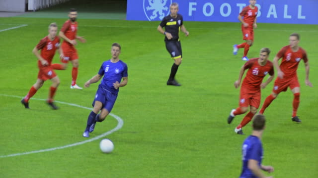Blue football team passing the ball at a match