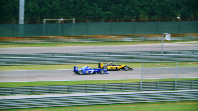 blue formula overtaking the red and yellow one in the race - crash helmet stock videos & royalty-free footage