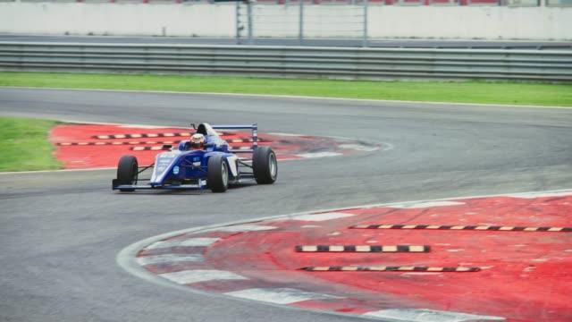 blue formula racing on the track - 曲線点の映像素材/bロール