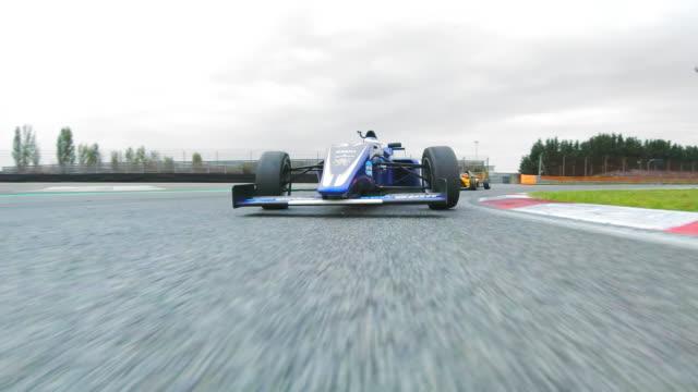 blue formula speeding on the racing track - crash helmet stock videos & royalty-free footage