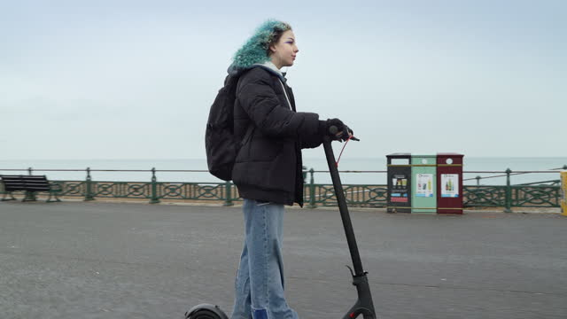 blue haired girl riding e scooter along seafront - female high school student stock videos & royalty-free footage