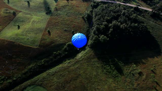 vídeos y material grabado en eventos de stock de globos de aire caliente volando azul - globo aerostático