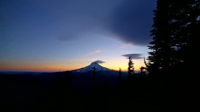 Blue hour dusk summit of Mt. Hood and blowing snow snowcapped snowy peak and forest cascades wide