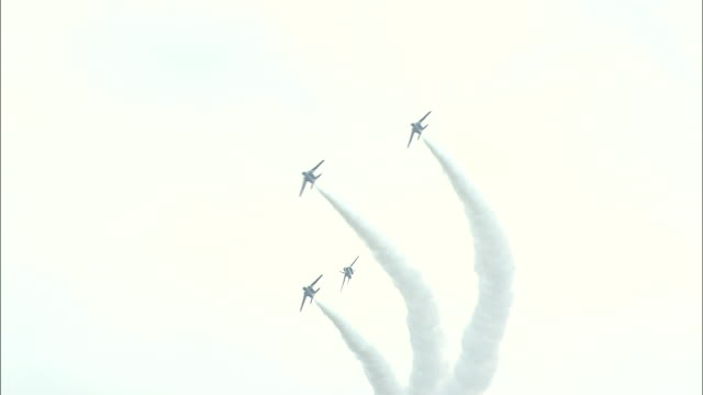 Blue Impulse jets perform aerobatics in a cloudy sky above the JASDF Chitose Air Base in Japan