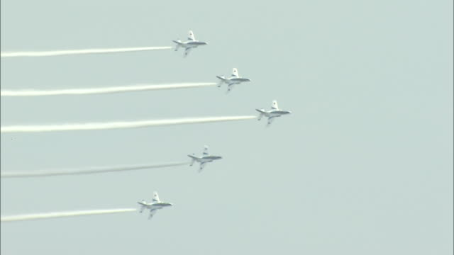 Blue Impulse jets streak across the sky leaving thick contrails as they perform aerobatics