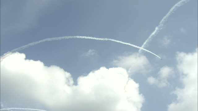 Blue Impulse planes perform aerobatics as they draw the Olympic symbol in the sky