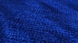 Blue knitted wool, pullover fabric is waving background. Close up, macro shot of fiber sweater