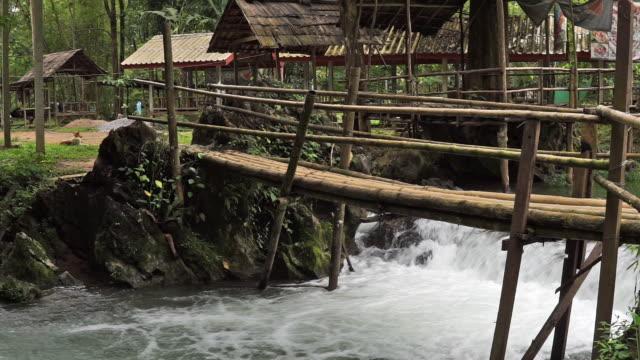 blue lagoon waterfall and bamboo bridge vang vieng laos - hut stock videos & royalty-free footage