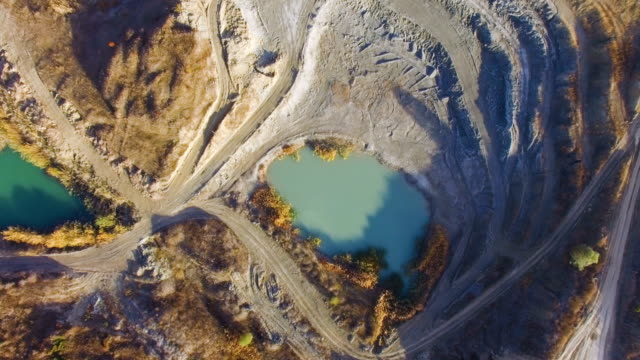 aerial: blue lake at the bottom of limestone quarry - mining stock videos & royalty-free footage