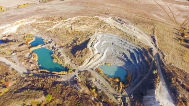 AERIAL: Blue lake at the bottom of limestone quarry