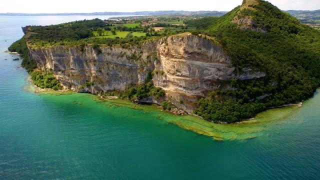 blu lago di garda con grande roccia veduta aerea - lago video stock e b–roll